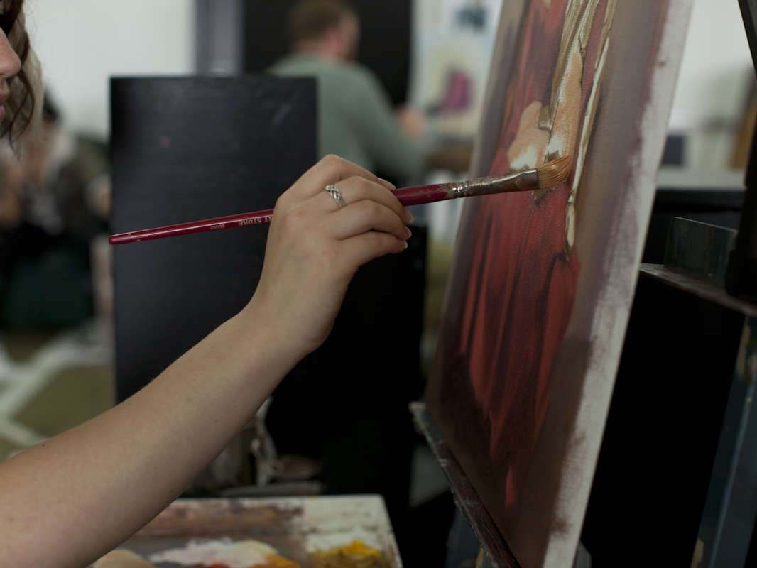 girl painting red on canvas