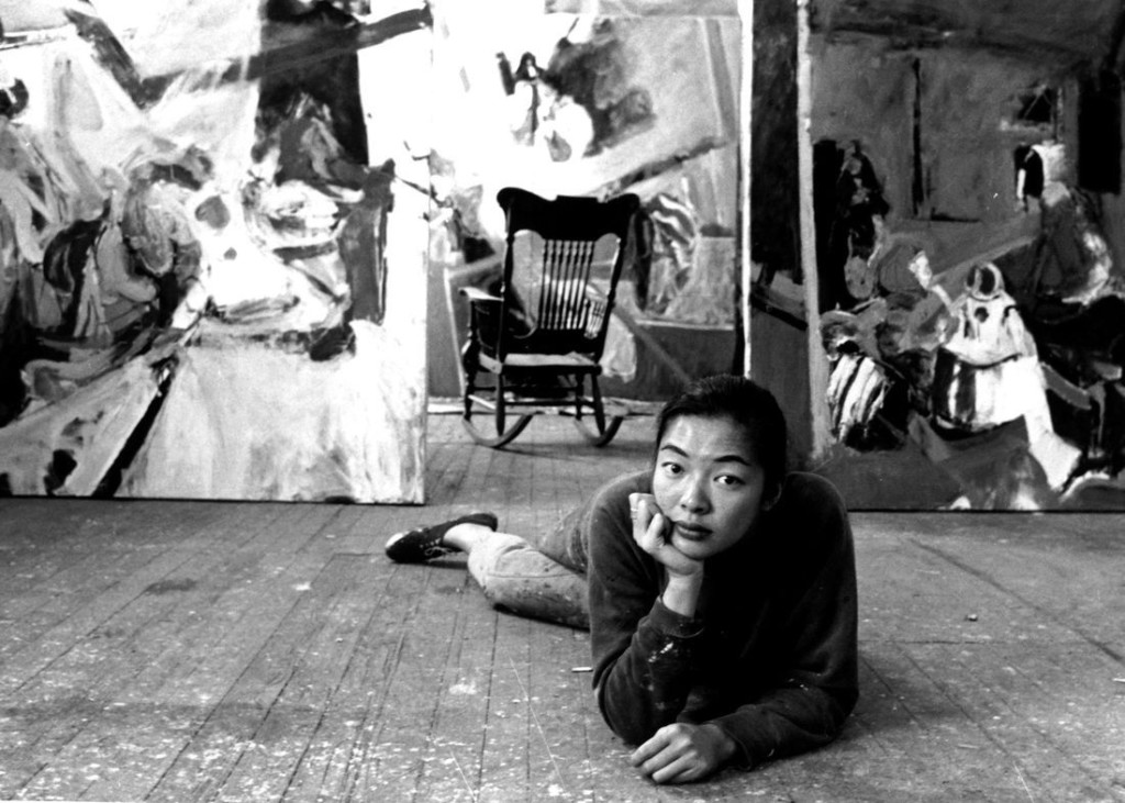 Bernice Bing poses on the floor in front of her paintings