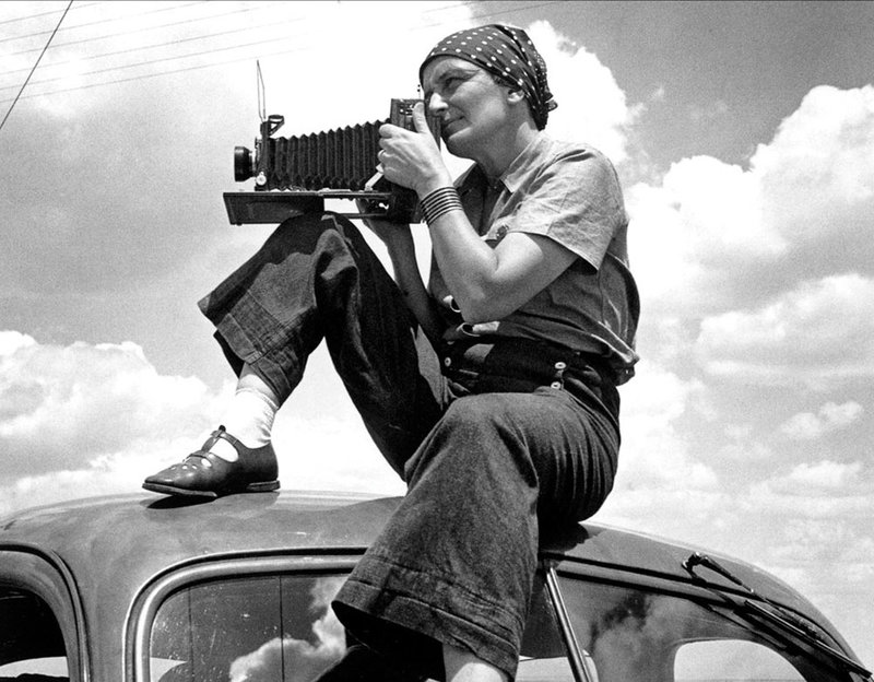Dorothea Lange with her camera on top of a car