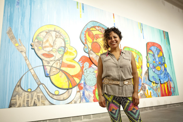 Favinanna Rodriguez in front of her art