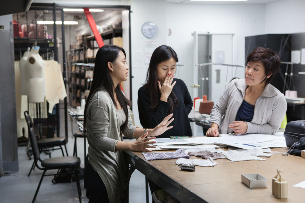 Fashion students collaborating with teacher