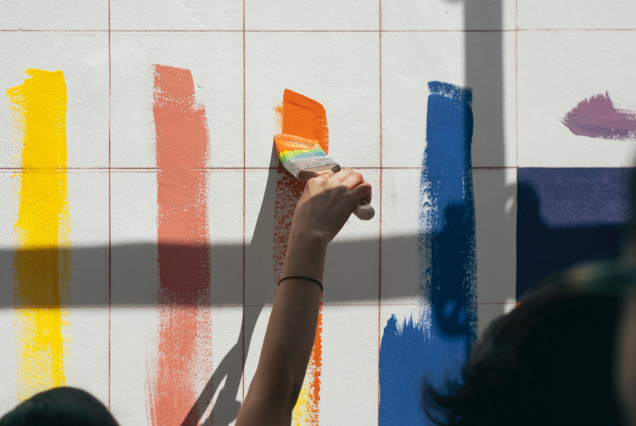 Painters using paint rollers to apply multiple lines of paint to a wall