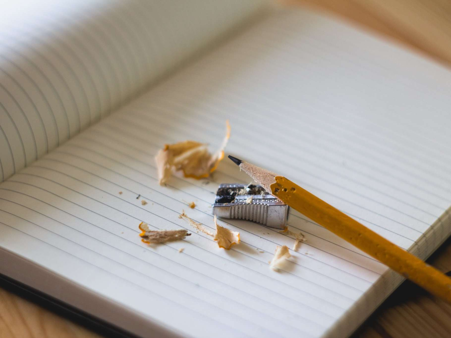 An image of a notebook with pencil shavings on top of it