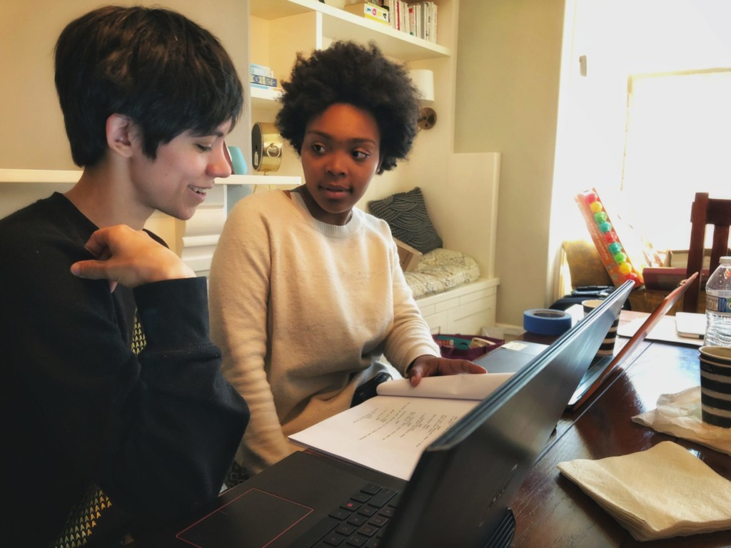 Two writing students discussing scripts on laptops