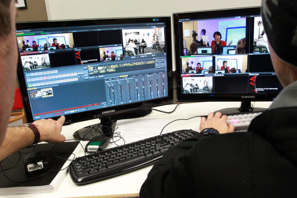 Communications student video editing with two computer screens