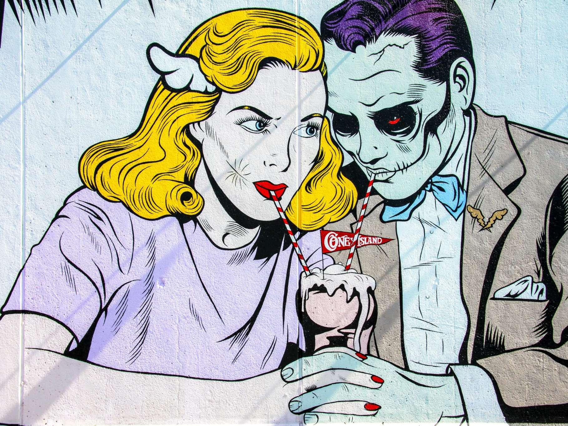 A comic book style man and woman sharing a milkshake
