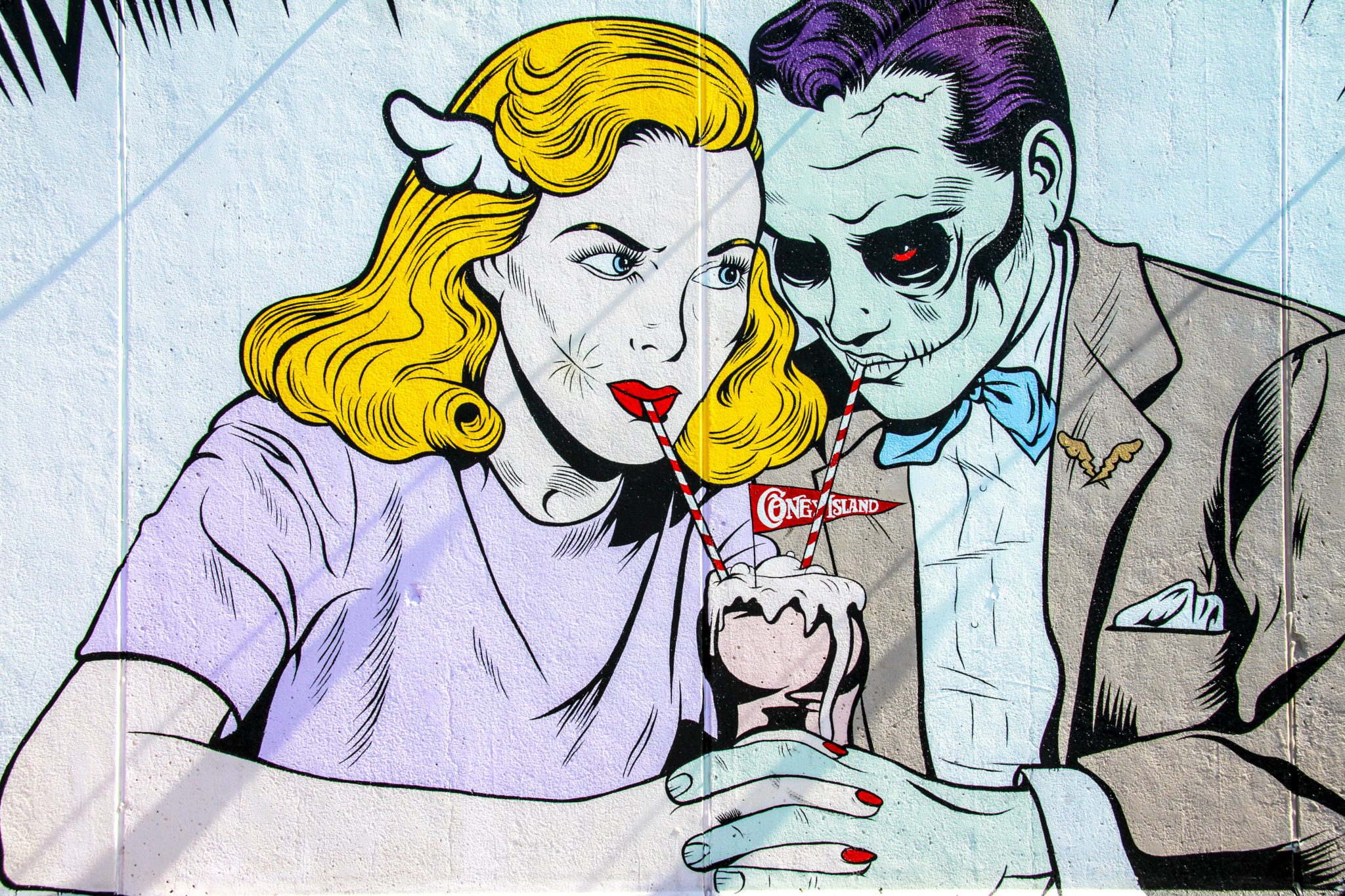 A comic book style man and woman sharing a milkshake