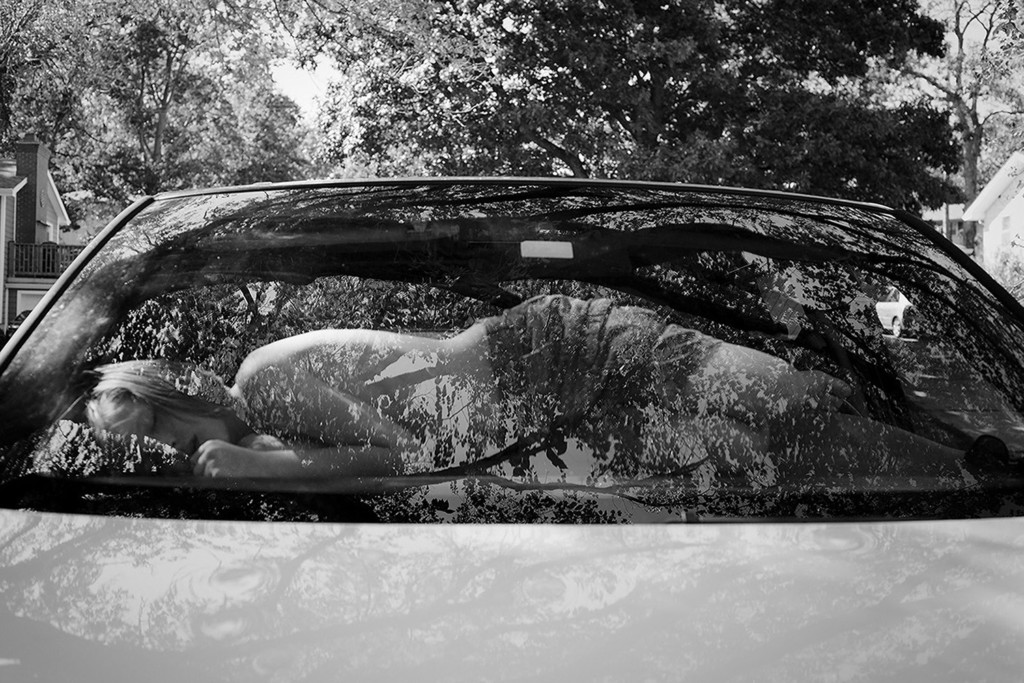 A child sleeping on the dashboard of a car