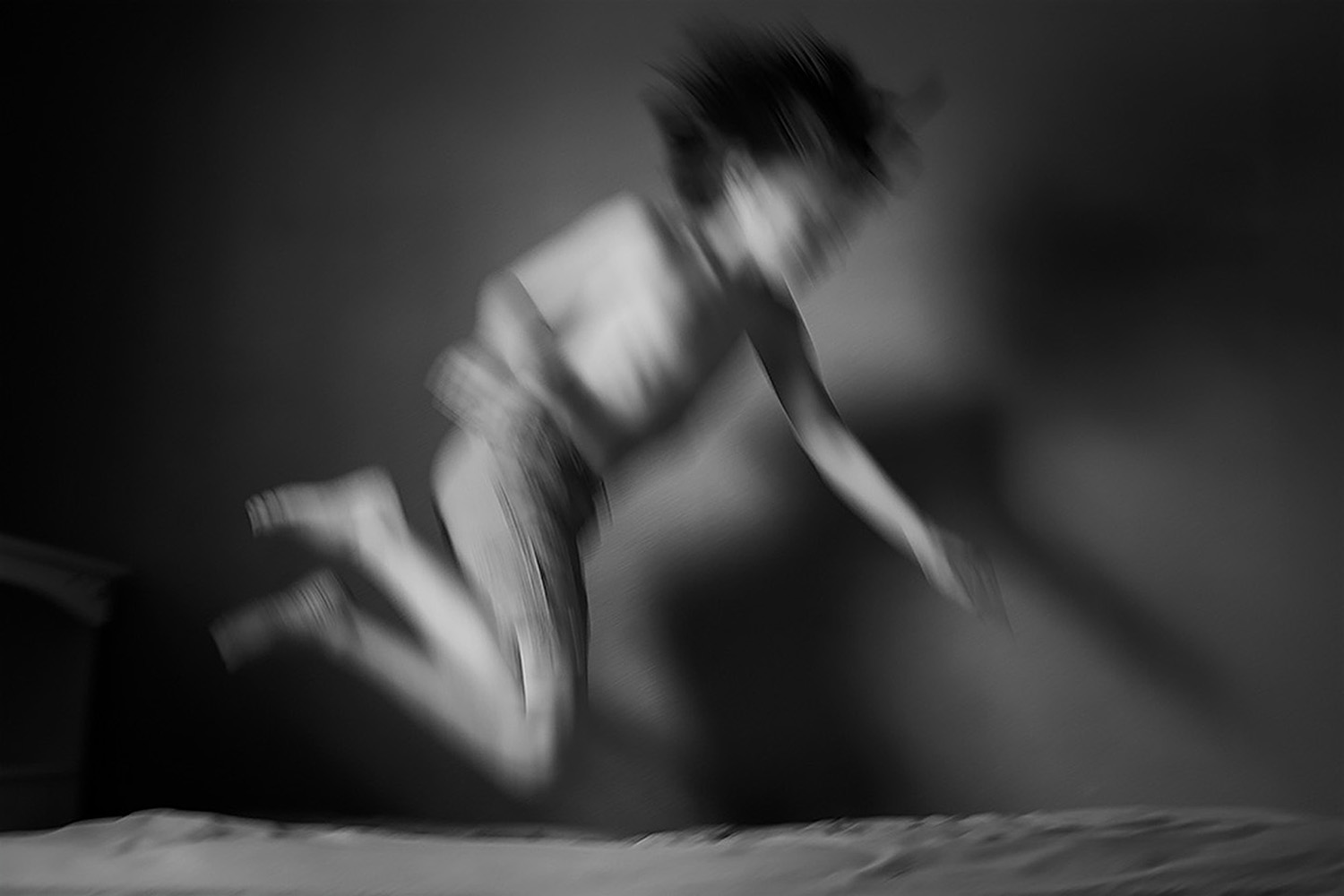Child leaping on a bed