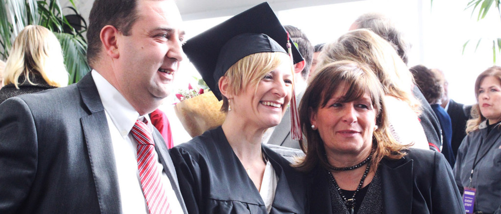 student with parents on graduation day