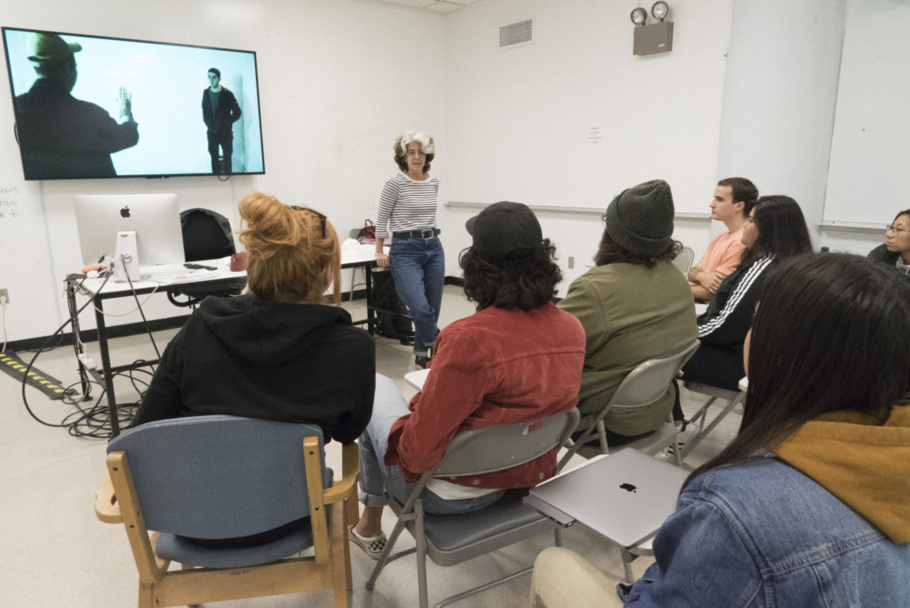 Instructor standing before a TV screen in a documentary class