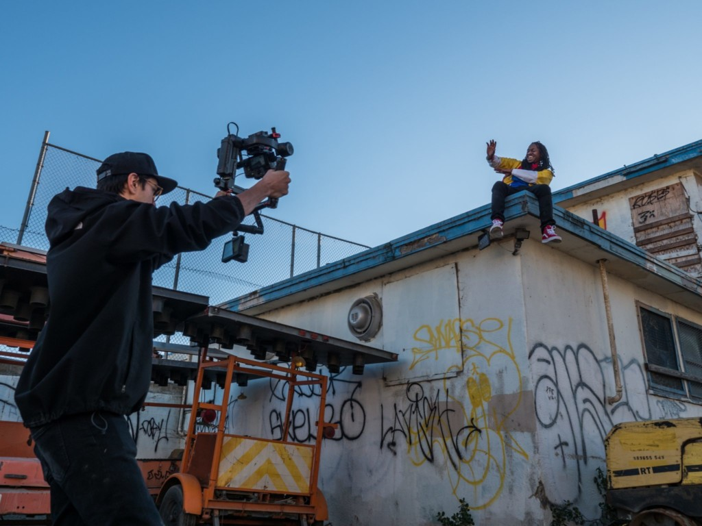 man filming a person on the roof