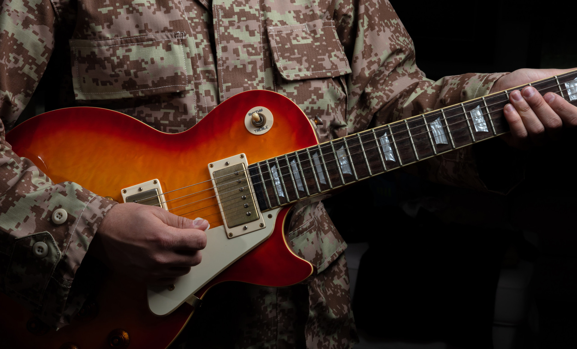 Soldier in uniform playing guitar