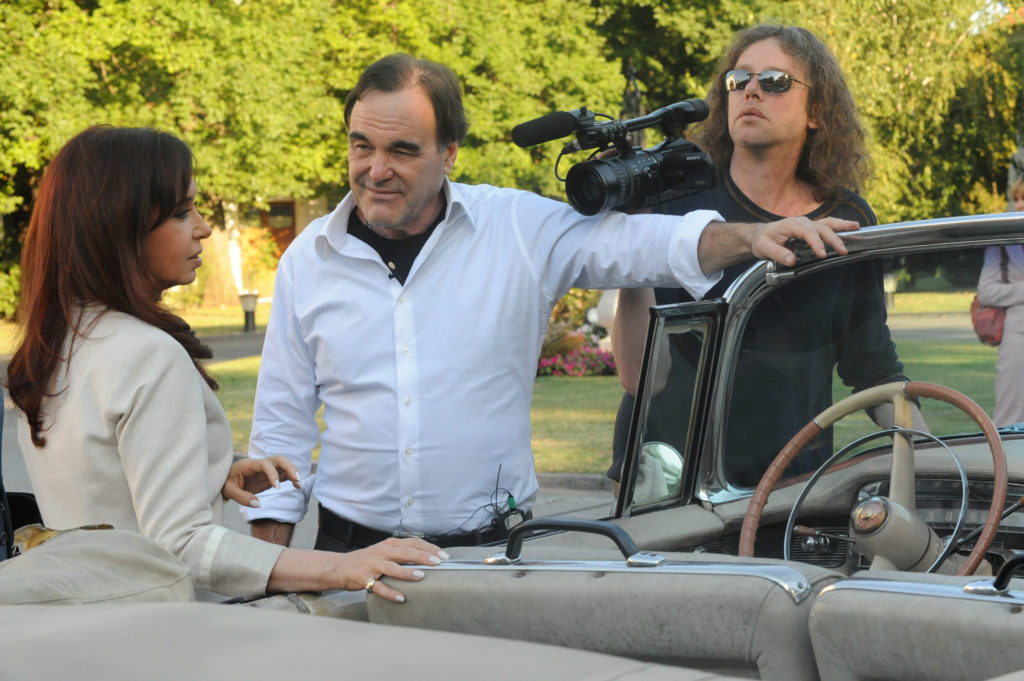 Photo of Oliver Stone standing with a movie camera near a vintage car
