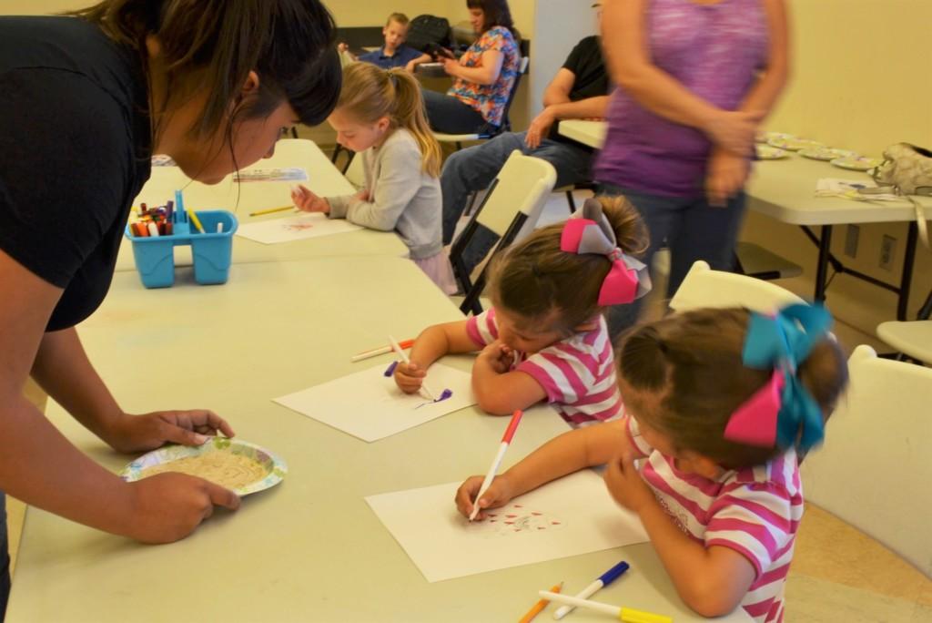 Teacher teaching art to young children