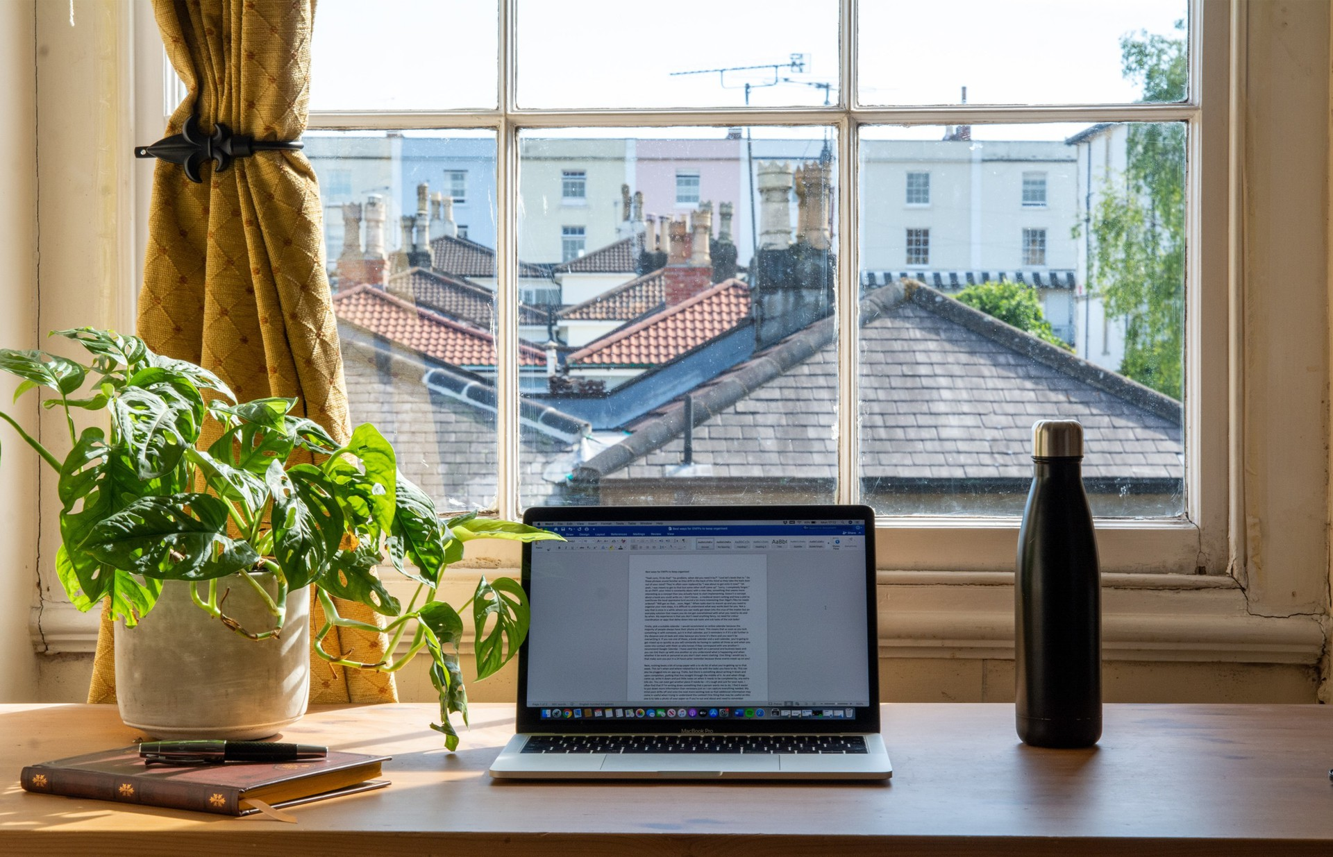Work-at-home desk space with computer, potted plant and water bottle in front of a window in daytime